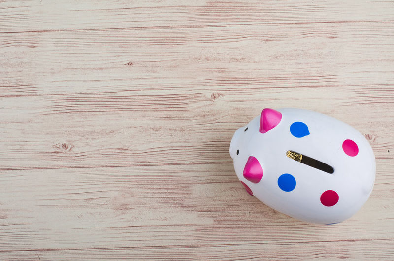 empty piggy bank over wooden background Indoors  Still Life Table Wood - Material High Angle View No People Close-up Directly Above Dice Arts Culture And Entertainment Blue Single Object Relaxation Leisure Activity Two Objects Representation Opportunity Multi Colored Leisure Games Human Representation Wood Grain