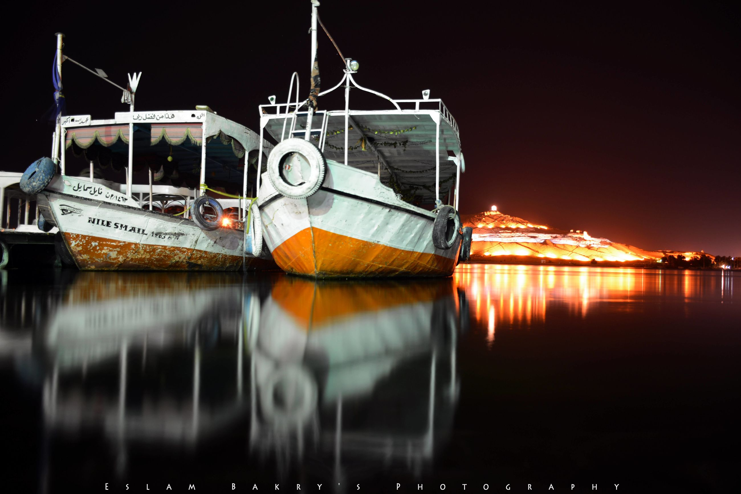 night, water, nautical vessel, illuminated, reflection, boat, transportation, waterfront, moored, river, mode of transport, lake, sky, no people, harbor, outdoors, built structure, building exterior, sea, clear sky
