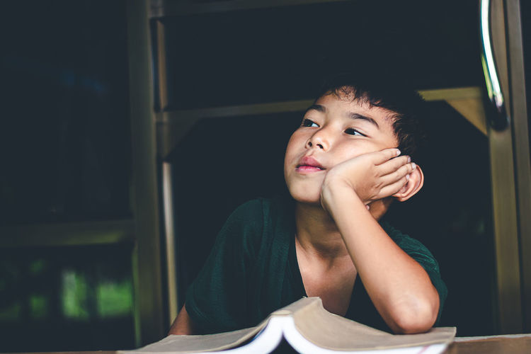 Portrait of boy looking away while sitting on table