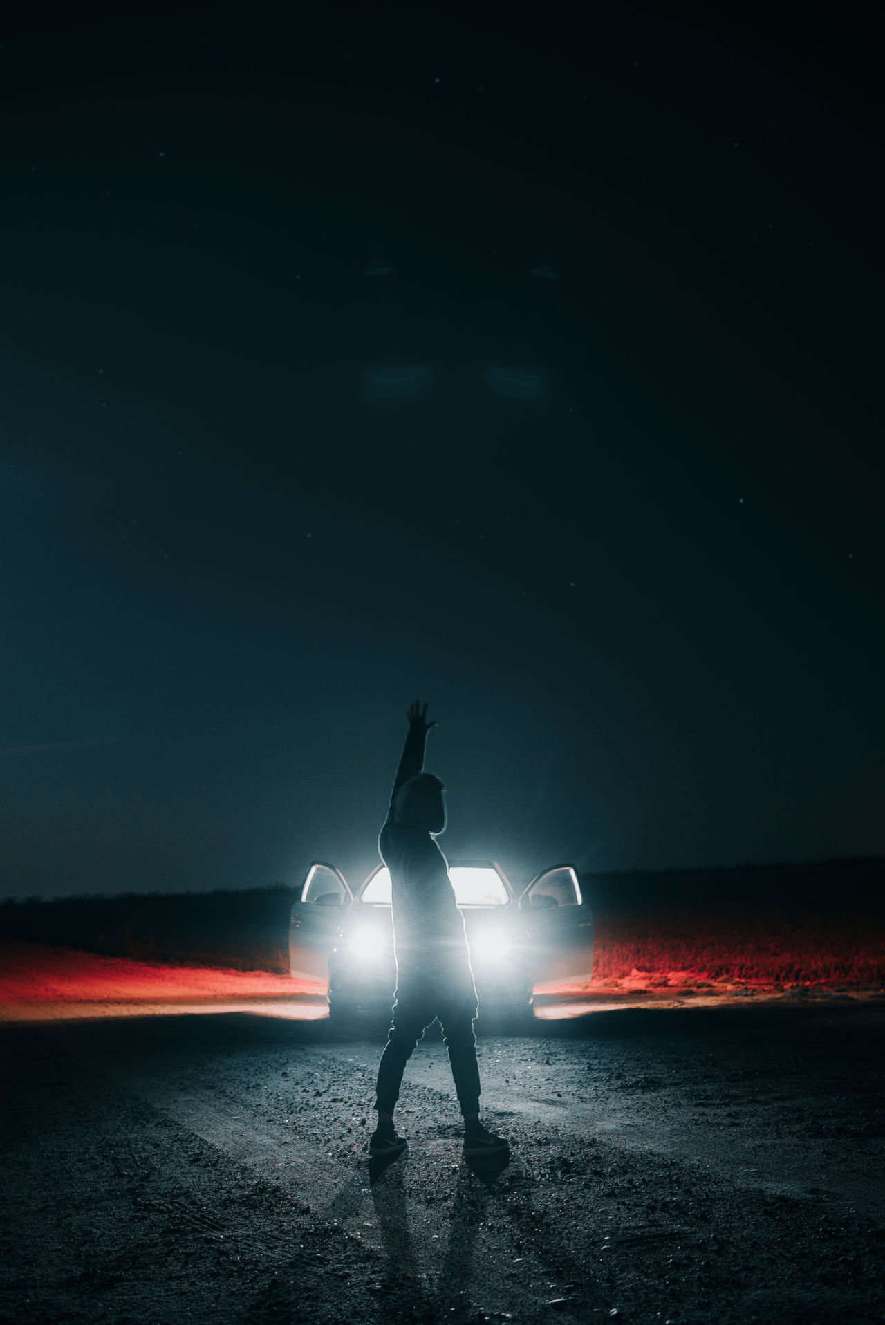 Person standing against illuminated car at night