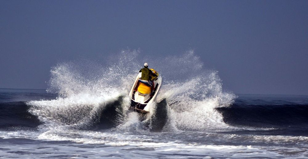 Rear view of man riding jet boat on sea against sky