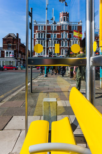 Yellow Empty Bench At Bus Stop In City