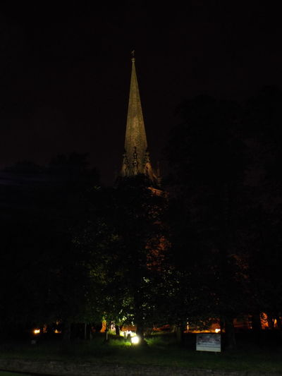Church lit up with lights behind the trees Behind The Trees Church Lit Up With Lights Church Steeple Night View Cities At Night Trees