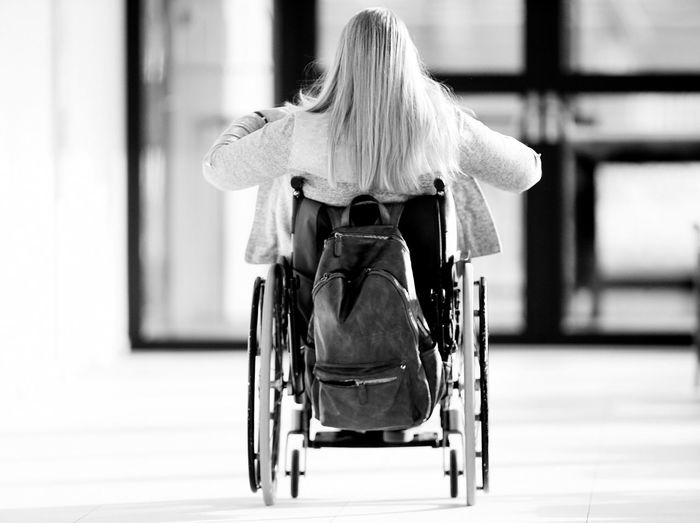 Rear view of woman with backpack sitting on wheelchair