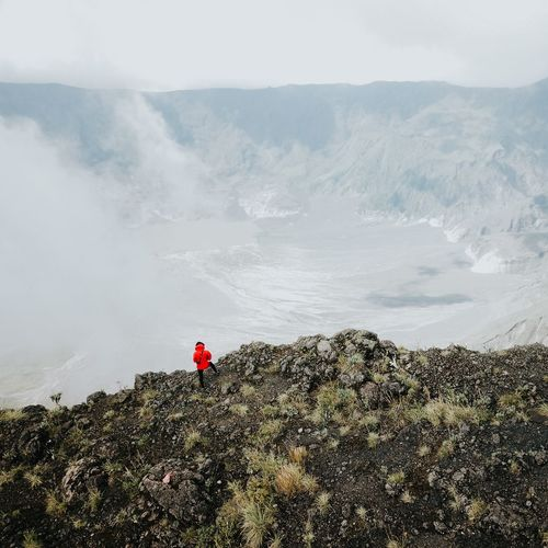 Man standing on rock against volcanic landscape