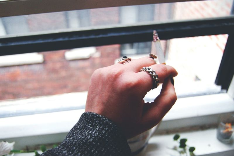 Cropped hand of woman smoking cigarette by window at home