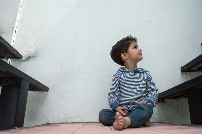 Boy looking away while sitting on wall