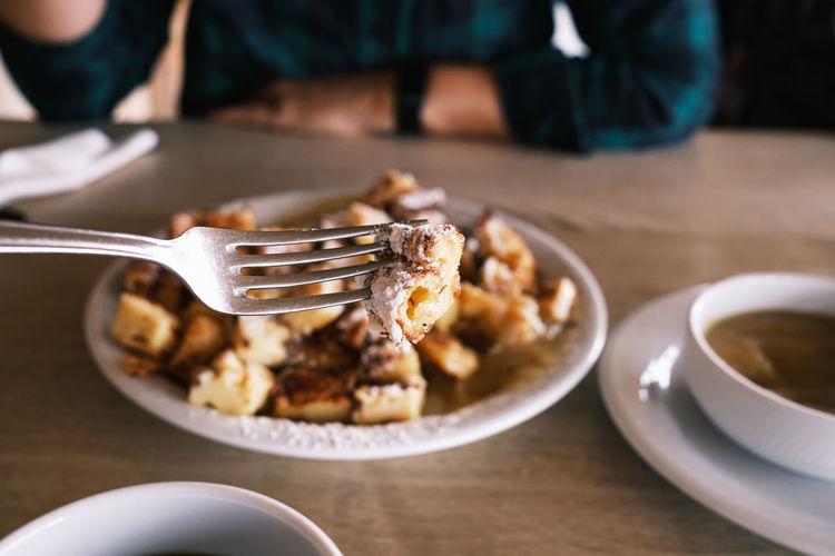 Fork picking piece of sweet cut-up pancake with raisins kaiserschmarrn