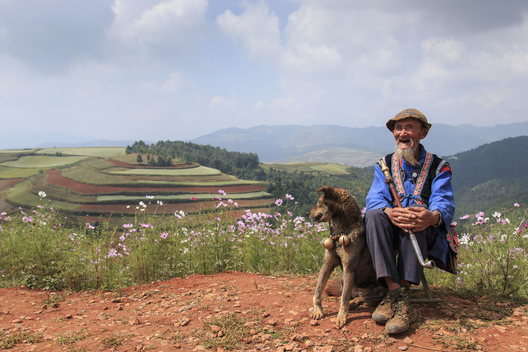 Dongchuan, China - September 27, 2016: An old chinese man dressed with the traditional attire smoking while enjoying the panorama of DongChuan in Yunnan Province, China Agriculture ASIA Casual Clothing China Chinese Minority Cloud Cloud - Sky Cropped Dongchuan Full Length Hill Landscape Leisure Activity Lifestyles Man Mountain Person Red Land Rural Scene Sky Smoking South East Asia Standing Terraces Traditional