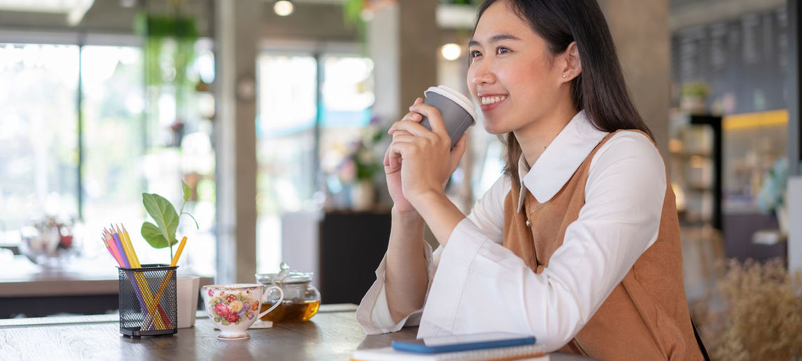 Midsection of woman drinking glass while sitting on table