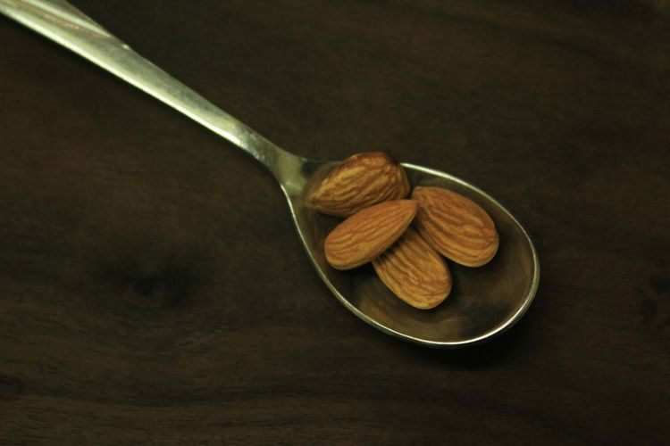 Studio Shot Food And Drink No People Food Photography Wooden Table Freshness Eating High Angle View Brown Background Energy Calories Dry Fruit Almond Colored Background Spoonful Spoonfull Wooden Table Food Indoors  Nut - Food Healthy Eating Close-up Almonds