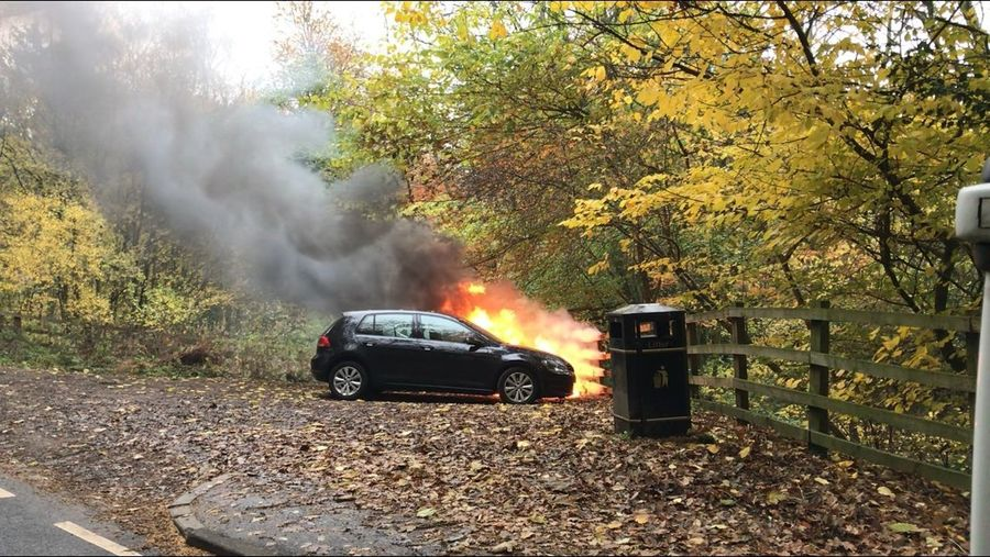 The car behind black Golf is on fire, though the Golf is probably burnt out too. Brigade on route Car Fire Mode Of Transportation Car Motor Vehicle Transportation Land Vehicle Nature Plant Smoke - Physical Structure Burning Fire Accidents And Disasters Flame Heat - Temperature