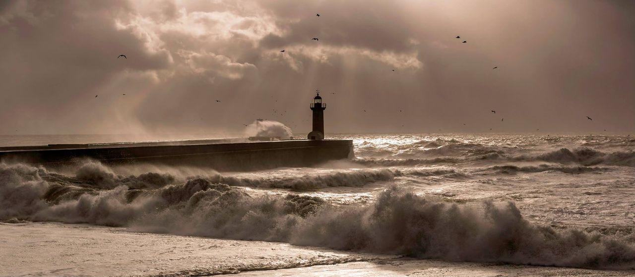 Silhouette Lighthouse Amidst Sea Against Cloudy Sky