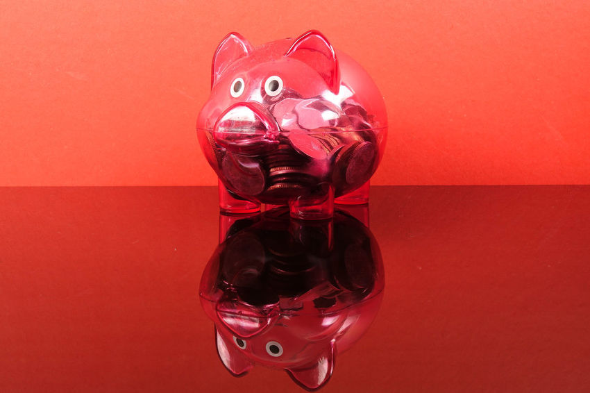 Saving concept with red piggy bank on red background. Piggy Bank Art And Craft Close-up Coin Colored Background Conceptual Photography  Craft Creativity Disguise Glass - Material Human Representation Indoors  Investment Mammal No People Red Representation Saving Concept Single Object Still Life Table Toy Transparent Wall - Building Feature