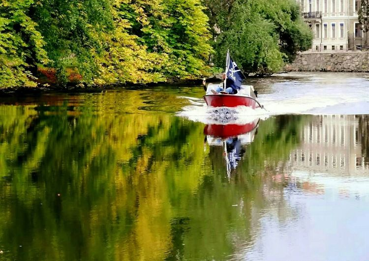 red color Autumn colors Houses Blue Color Cityscape Canal Jolly Roger Red Color #urbanana: The Urban Playground Flag Water Tree Reflection Architecture Building Exterior Nautical Vessel Boat Water Vehicle Rippled Fluttering Flag Pole