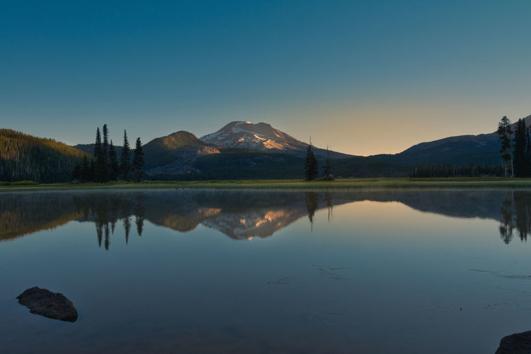 Sparks Lake in Central Oregon near Bend, is a popular destination for outdoor enthusiasts Beauty In Nature Clear Sky Copy Space Idyllic Lake Mountain Mountain Range Nature No People Non-urban Scene Outdoors Reflection Scenics - Nature Sky Sparks Lake Sunset Symmetry Tranquil Scene Tranquility Water Waterfront