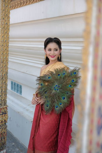 Smiling young woman wearing traditional clothing holding peacock feathers against wall