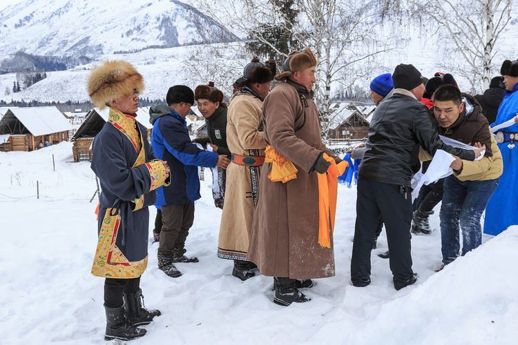 Hemu, Xinjiang - February 16, 2018: Tuva people, one of the minorities in China, performing a religious rite in Hemu village ASIA Altai Mountains Bactrian Camel Ice Kanas Lake Urumqi XinJiang Altai China Grassland Hasake Minority Hemu Village Horse Racing Kanas Ski Country Snow Tuva Minority
