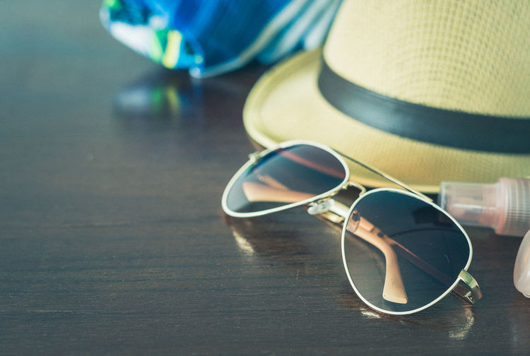 Glasses and hats are on the table for travel concepts. Table Still Life Glasses Close-up Personal Accessory No People Sunglasses Fashion Indoors  Security Focus On Foreground Protection Hat Wood - Material Eyeglasses  Selective Focus Day Glass - Material Safety Eyewear