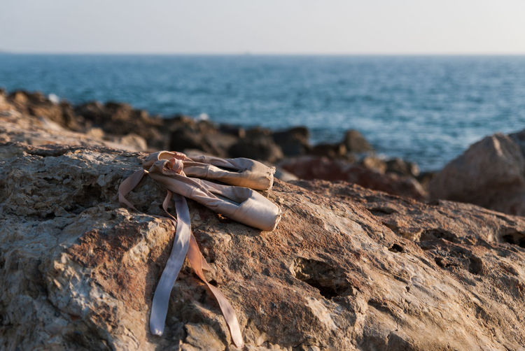 Close-up of abandoned ballet shoes on rock formation with sea in background