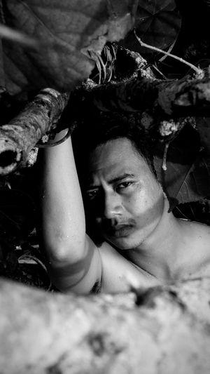 Portrait of shirtless man amidst plants