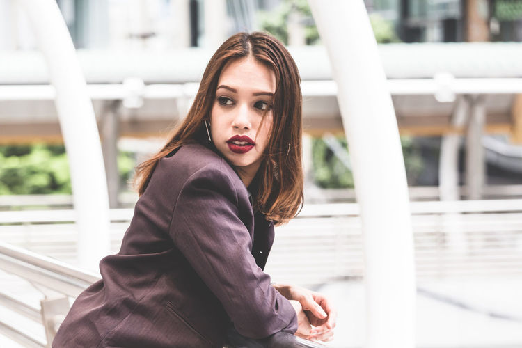 Young businesswoman standing on elevated walkway