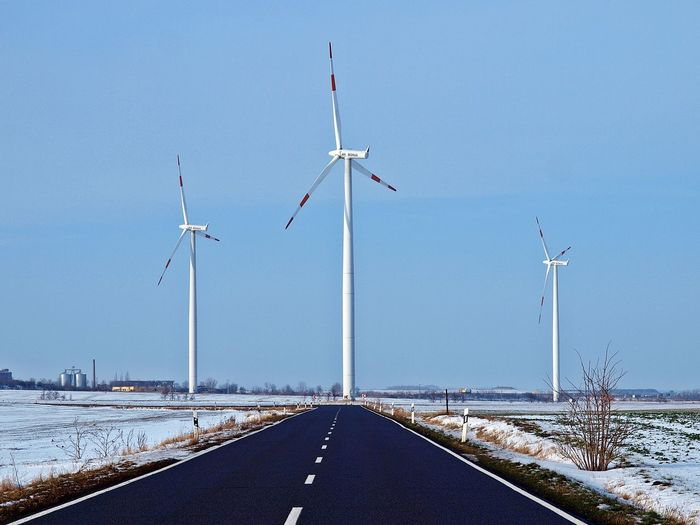 Empty road leading towards windmills against sky during winter