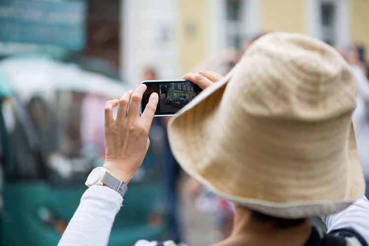 Rear view of woman wearing hat photographing with mobile phone