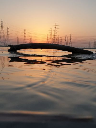 Silhouette electricity pylon by bridge against sky during sunset