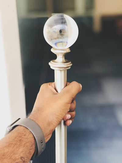 Close-up of hand holding metal rod with crystal ball on top