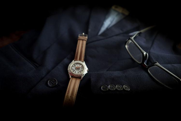 Close-up of wristwatch by eyeglasses on blazer