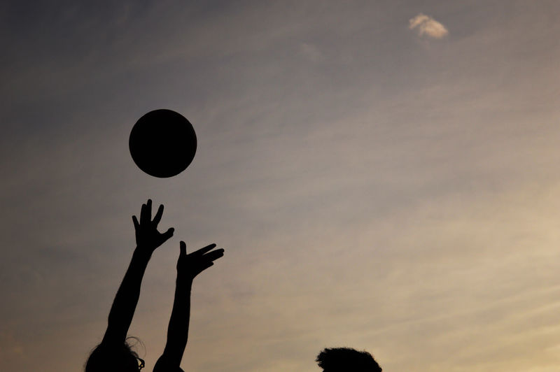 Cropped image of friends playing basketball against sky during sunset