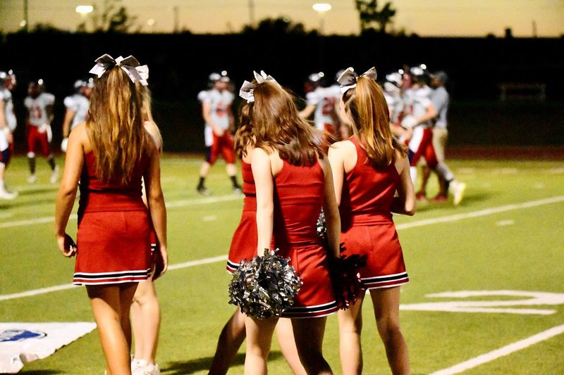 Rear view of cheerleaders on football stadium