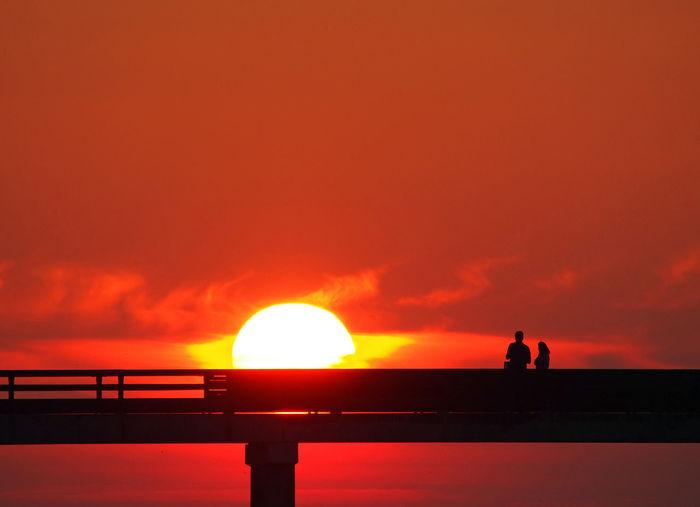 Silhouette people on bridge against orange sky