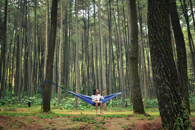 Full Length Of Woman Sitting In A Hammock