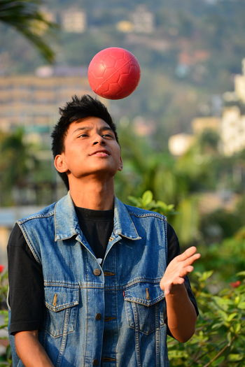 Close-Up Of Young Man Playing With Ball While Standing Against Plants