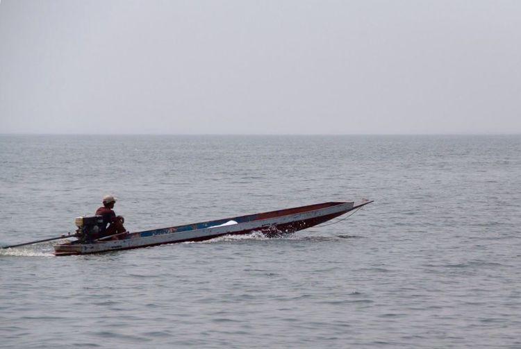 Man rowing boat in sea against sky