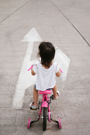 Rear View Of Girl Riding Tricycle