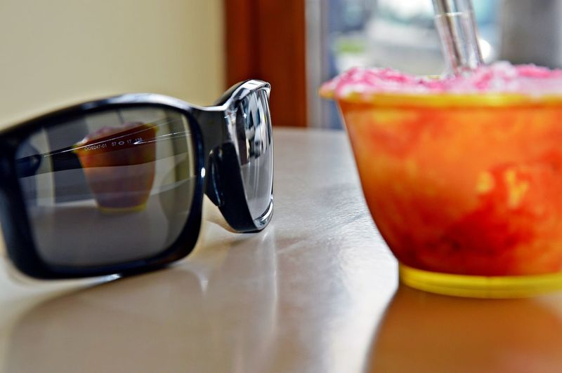 Close-up of fresh ice cream with reflection on sunglasses at home