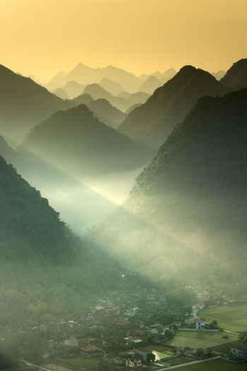 The magical scene of the mountains resemble the successive message they are covered with layers of lush green vegetation at dawn in Bac Son district Lang Son Province, Vietnam Magical Morning Tourist Travel Weather Beauty In Nature Cloud - Sky Environment Fog Idyllic Landscape Majestic Mountain Mountain Peak Mountain Range Nature No People Non-urban Scene Outdoors Scenery Scenics - Nature Sky Sunset Tranquil Scene Tranquility