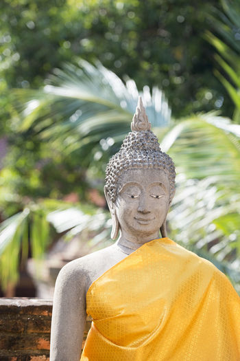 Old Buddha Statue Against Trees At Wat Yai Chai Mongkhon