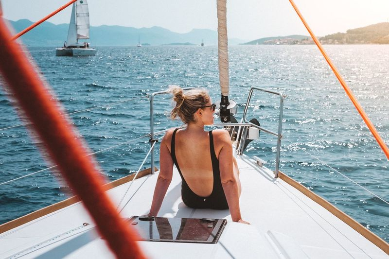 Rear View Of Woman Traveling In Yacht Sailing On Sea