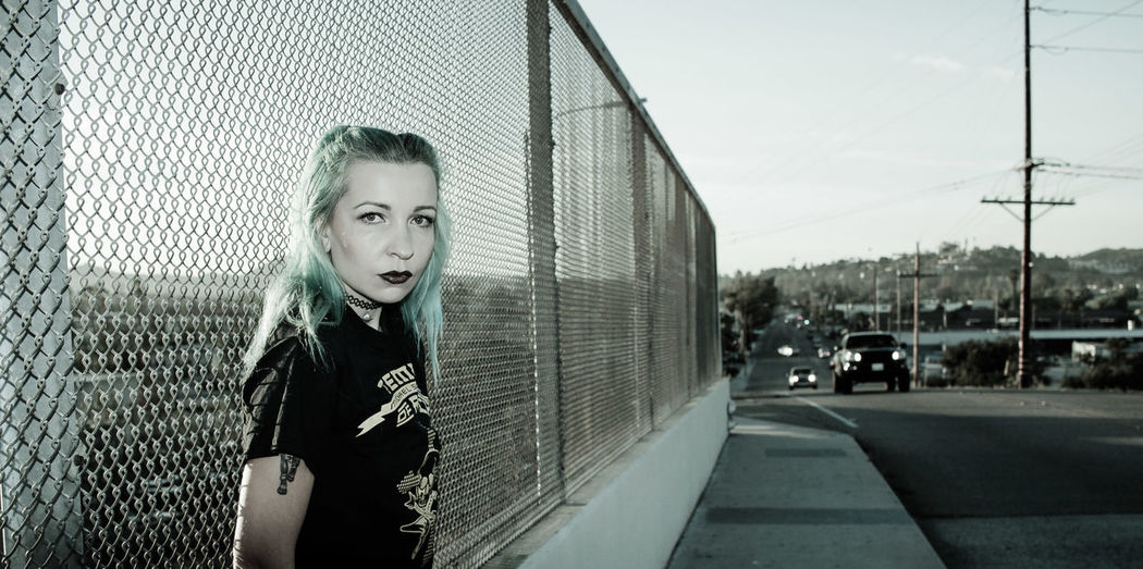 Portrait of female punk standing on sidewalk by road against fence