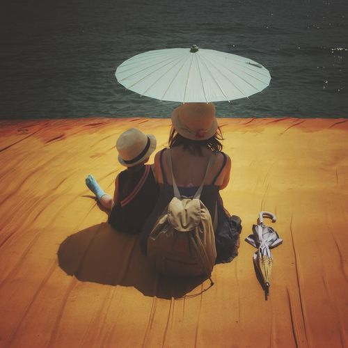 Walking on the Floating piers | Mother Fine Art Close-up Point Of View Golden Moments  Tailored To You Christo And The Floating Piers Getting Inspired Original Experiences The Essence Of Summer Still Life TK Maxx Socksie Nature People The Floating Piers Sunshine Feel The Journey The OO Mission Relaxing 43 Golden Moments Showcase July Edge Of Imagination Umbrellas Lago D'Iseo EyeEm Italy |