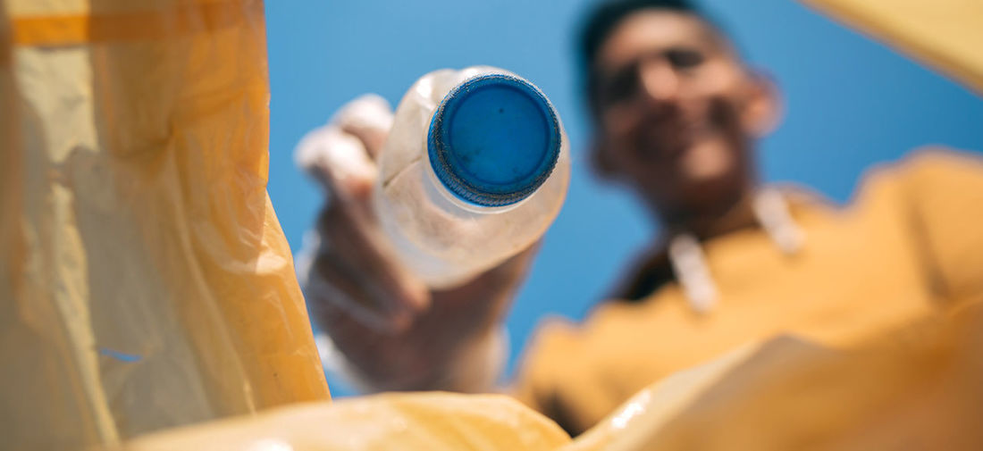 Close-up of man holding plastic bottle