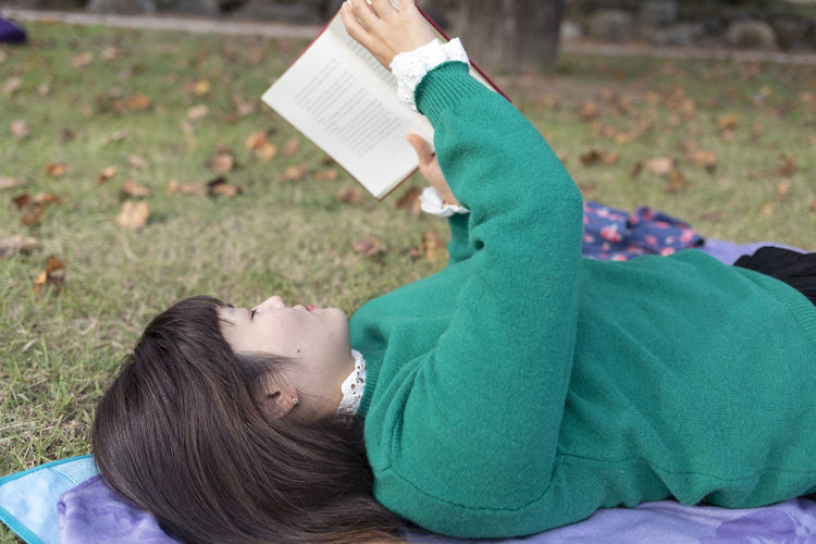 Rear view of woman lying on book
