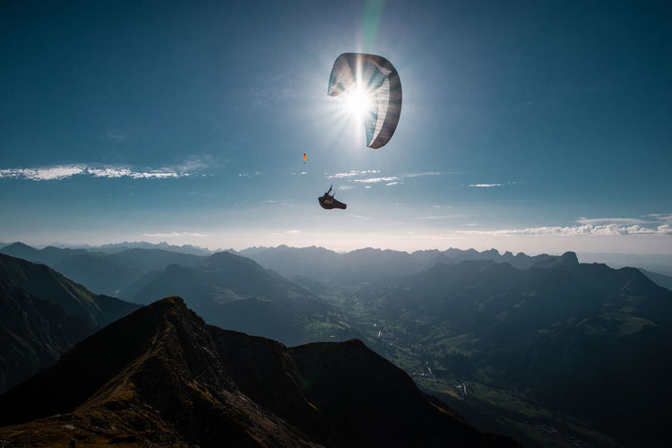 Man paragliding over mountains against sky during sunny day