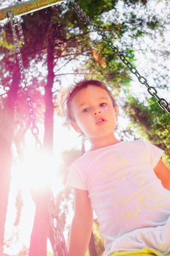A girl at the swing. Back To Childhood  Backlight Backlight Portrait Bottom Angle Bottom Up Confused Confused Outlook Face Expression Flashback Girl Portrait Girl Swinging Girls Memories Nice Catch Nice Moments Playing In The Nature Sun Shadow Swinging Natural Light EyeEmNewHere The Portraitist - 2017 EyeEm Awards