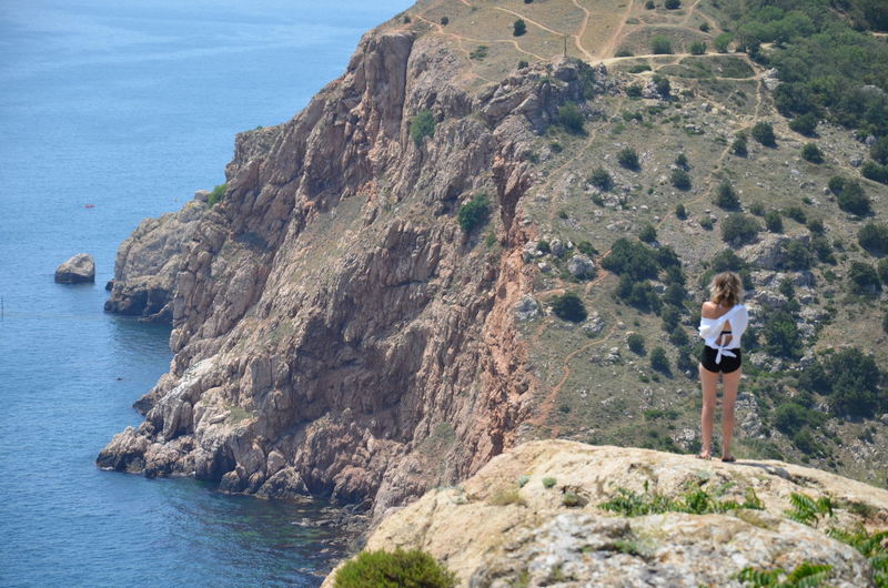 Wife standing on rock by sea