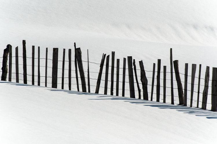 Silhouette fence on snow covered field